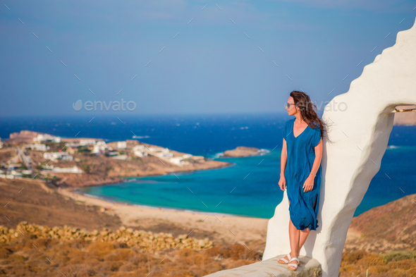 Young woman and traditional white church with sea view in Mykonos island,Greece - Stock Photo - Images