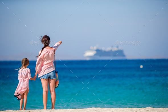 Young beautiful mother and her adorable little daughter at tropical beach looking at the sea - Stock Photo - Images