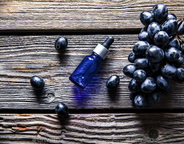 Essential oil of grape, vine, blue grapes, old wooden background, fruit. food - Stock Photo - Images