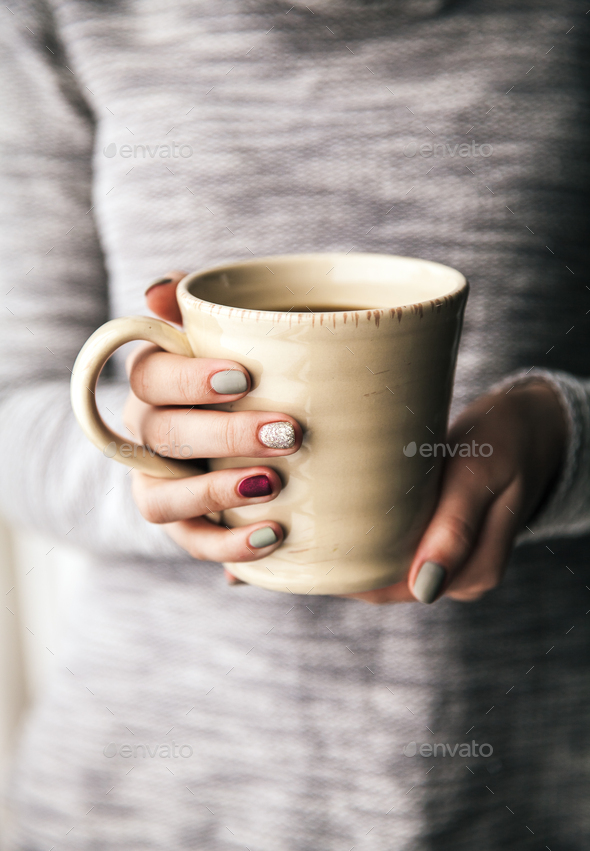 Close-up of a woman's hand holding a cup of hot coffee. fashion, leisure - Stock Photo - Images