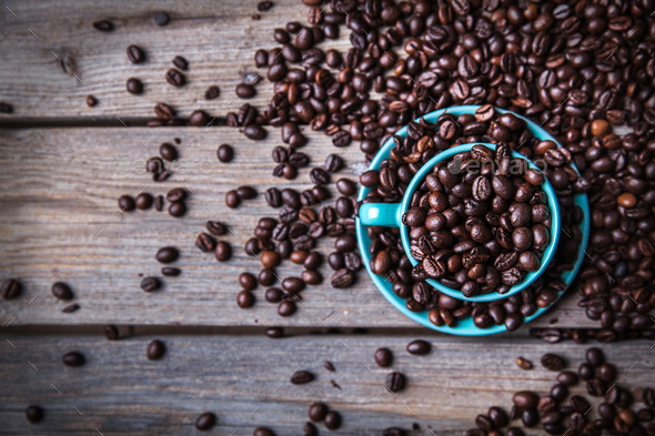 Turquoise cup with coffee beans on a wooden background. Beverage, tableware - Stock Photo - Images