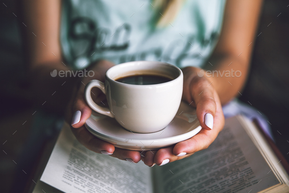 Girl with a cup of coffee and a book. Wakes up, morning, break, hobbies - Stock Photo - Images