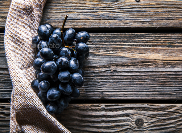 Blue grapes with a kitchen towel on wooden background. Food, Fruits - Stock Photo - Images