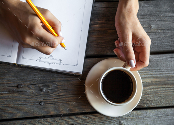 Female hand with a cup of coffee, taking notes. It works records. Business - Stock Photo - Images