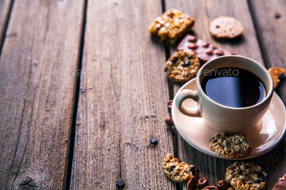cup of coffee with a delicious chocolate and cookies on a wooden background - Stock Photo - Images
