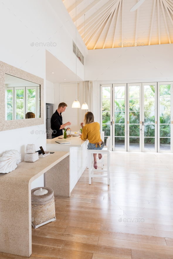 Couple cooking on a white island kitchen at home - Stock Photo - Images