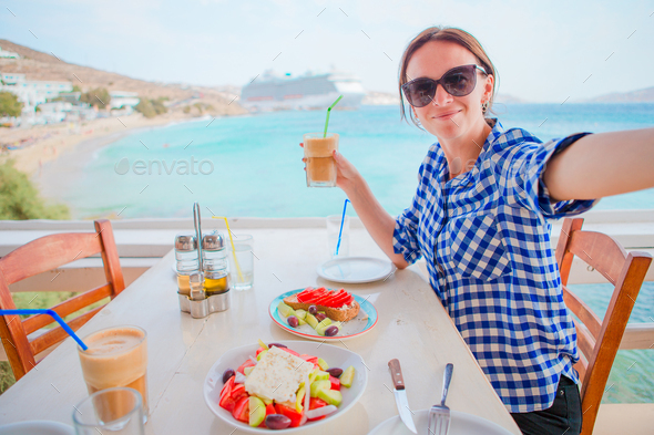Young woman having lunch with delicious fresh greek salad, frappe and brusketa served for lunch at - Stock Photo - Images
