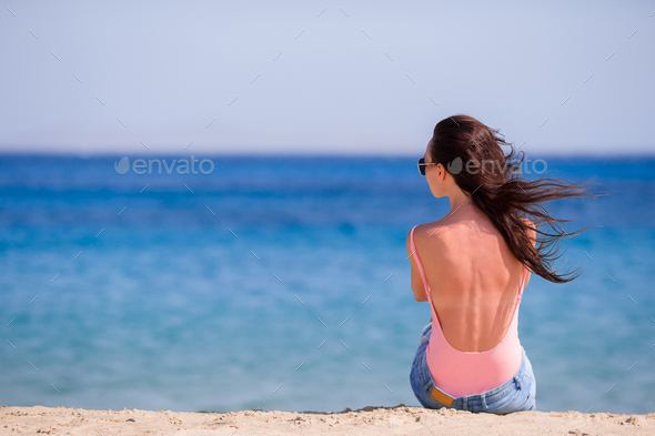 Young beautiful woman with coffee on the beach during tropical vacation. Girl enjoy her wekeend on - Stock Photo - Images