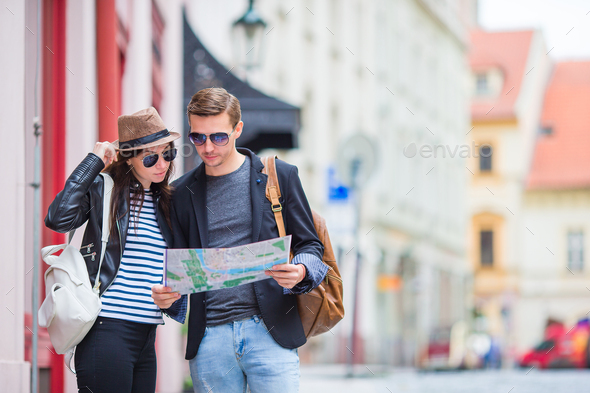 Young tourist couple traveling on holidays outdoors smiling happy. Caucasian family with city map in - Stock Photo - Images