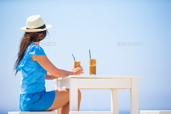 Young woman drinking cold coffee enjoying sea view. Beautiful woman relax during exotic vacation on - Stock Photo - Images