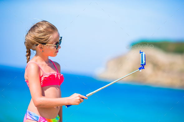 Little girl taking selfie by her smartphone on the beach. Kid enjoying her suumer vacation and - Stock Photo - Images