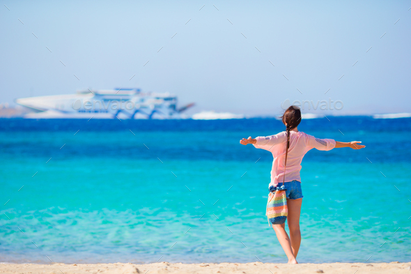 Young girl on the beach background big cruise liner. Woman enjoy her wekeend on one of the beautiful - Stock Photo - Images
