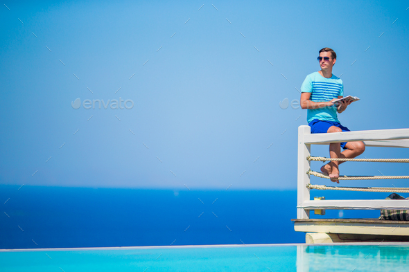 Caucasian guy relaxing near pool with amazing view and reading book in Greece. Beautiful famous - Stock Photo - Images