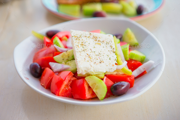 Delicious fresh greek salad served for lunch at outdoor restaurant with beautiful view on the sea - Stock Photo - Images