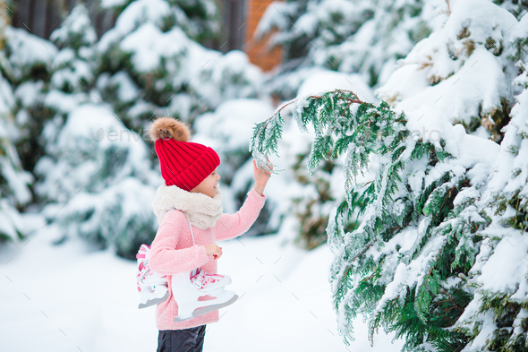 Adorable little girl going skate in winter snow day outdoors - Stock Photo - Images