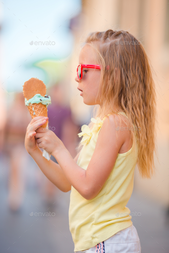 Adorable little girl eating ice-cream outdoors at summer. Cute kid enjoying real italian gelato near - Stock Photo - Images