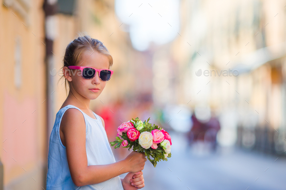 Adorable little girl with flowers bouquet walking in european city - Stock Photo - Images
