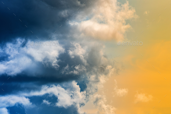 Dramatic Blue Thunderclouds, Stunning Yellow-Golden Fluffy Clouds Illuminated by Rays of Sun - Stock Photo - Images