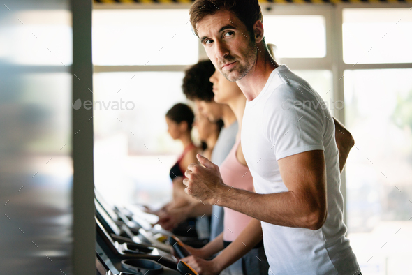 Fit people running in machine treadmill at fitness gym - Stock Photo - Images