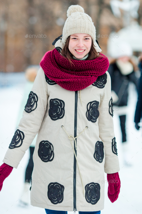Happy young woman skating on ice rink outdoors - Stock Photo - Images