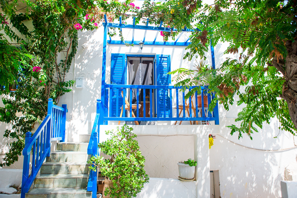Traditional houses with blue doors and windows in the narrow streets of greek village - Stock Photo - Images