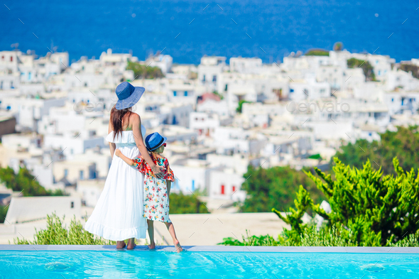 Adorable little girl and young mother in outdoor swimming pool background Mykonos town on Cyclades - Stock Photo - Images