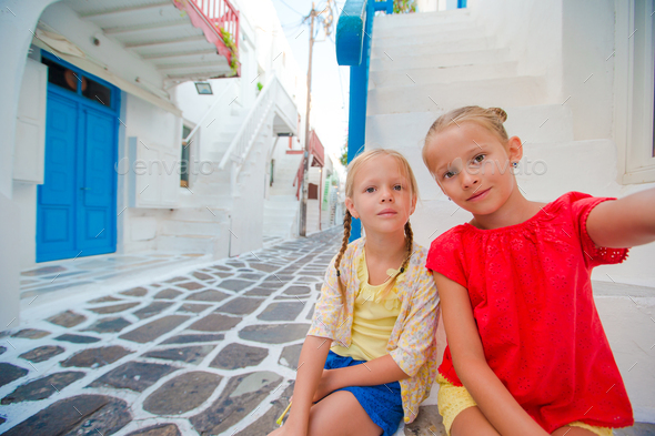 Two girls taking selfie photo outdoors in greek village on narrow street - Stock Photo - Images