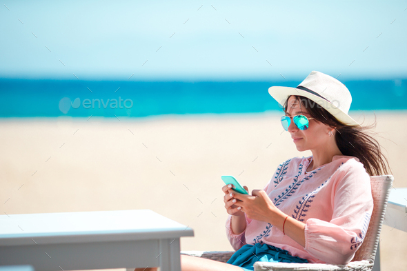 Woman with cellphone outdoors on the beach. Tourist using mobile smartphone - Stock Photo - Images