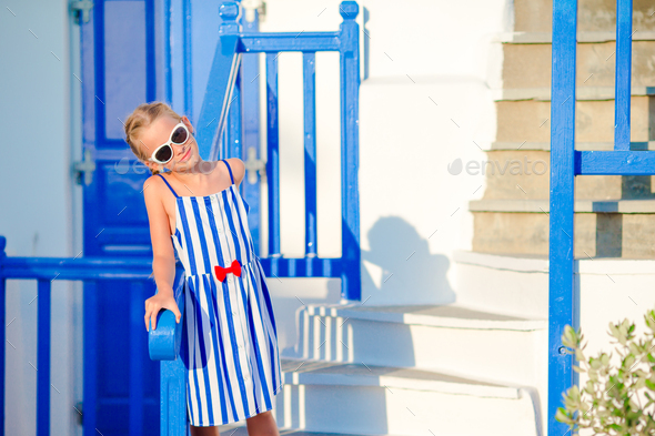 Little adorable girl at street of typical greek village with white walls and colorful doors on - Stock Photo - Images