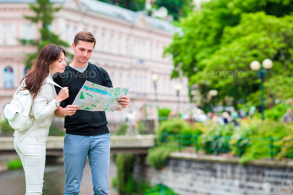 Couple traveling on their honeymoon in Europe. Caucasian family with city map in search of - Stock Photo - Images