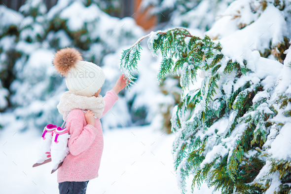 Adorable little girl going to skate in warm winter snow day outdoors - Stock Photo - Images