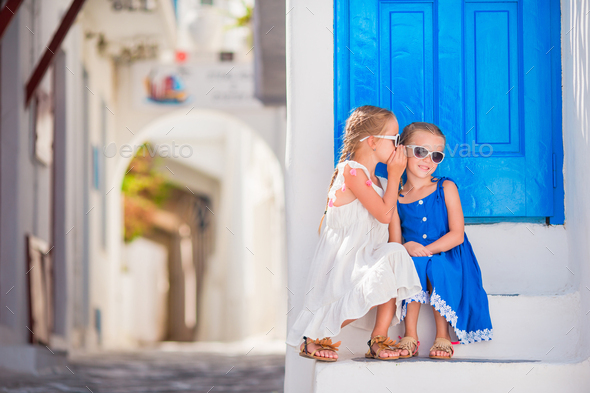 Little girls at street of typical greek traditional village on Mykonos Island, in Greece - Stock Photo - Images