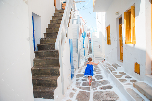 Adorable little girl at street of typical greek traditional village on Mykonos Island, in Greece - Stock Photo - Images