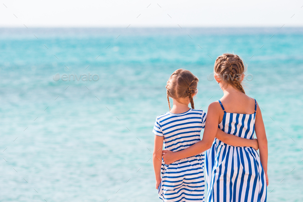 Back view of two girlson the beach background blue sea - Stock Photo - Images