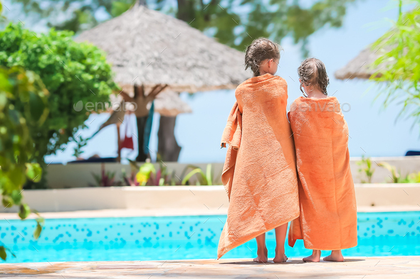 Adorable little girls wrapped in towel on the edge of pool - Stock Photo - Images