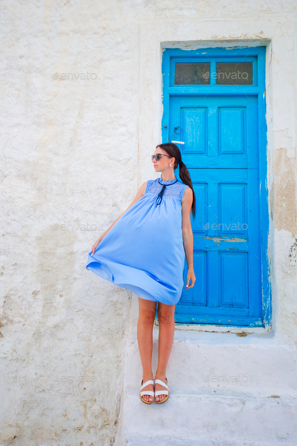 Happy woman on deserted streets of greek village. Young beautiful woman on vacation exploring - Stock Photo - Images