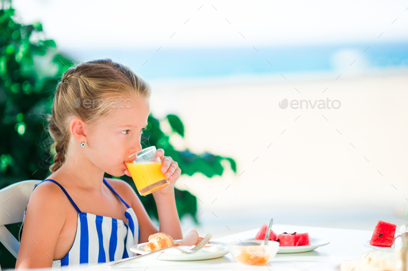 Adorable little girl having breakfast at cafe with sea view - Stock Photo - Images