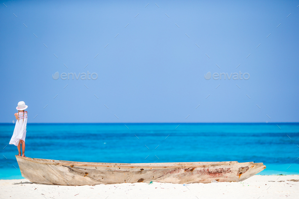 Adorable little girl on boat on the shore - Stock Photo - Images