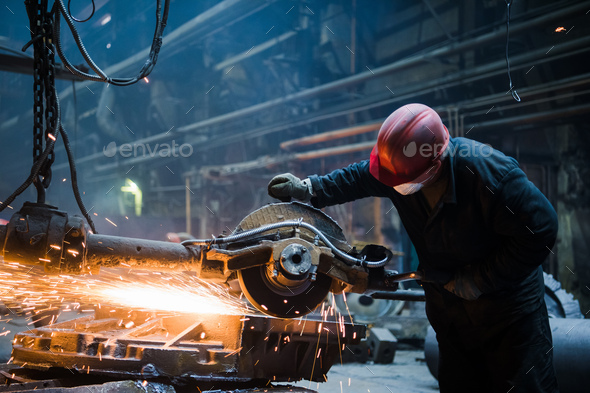 Male worker wearing special protective gloves, cutting metal with big electric grinder, orange - Stock Photo - Images
