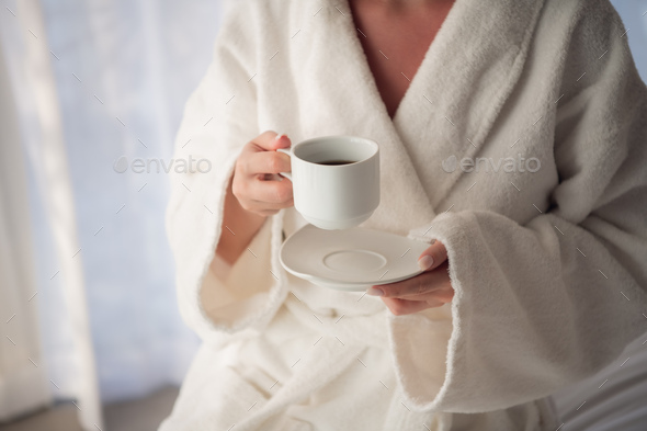 Attractive young girl in bathrobe holding a cup, looking at window and smiling while sitting on a - Stock Photo - Images