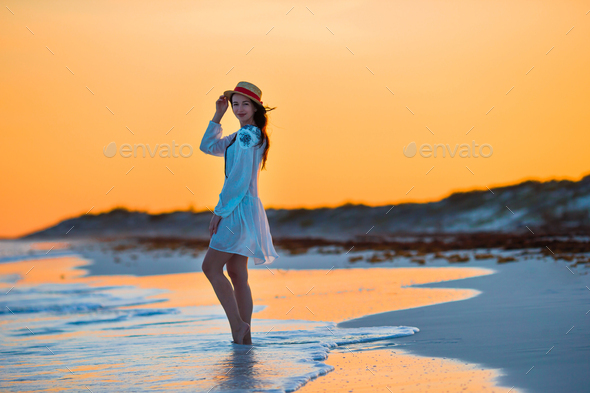 Young beautiful woman on tropical seashore in sunset. Happy girl in dress in the evening on the - Stock Photo - Images