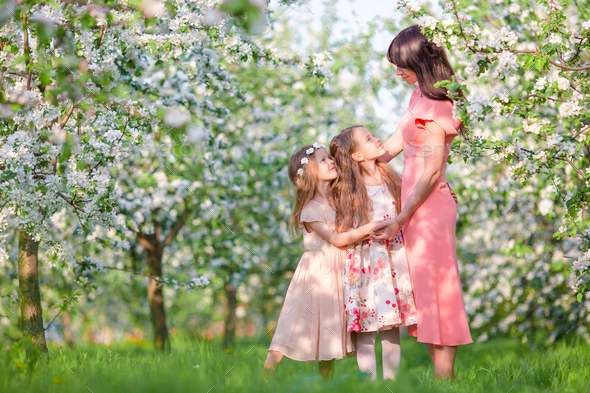 Family in blooming apple garden outdoors - Stock Photo - Images