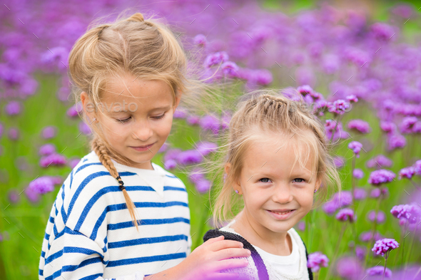 Little adorable girls walking outdoors in flowers field - Stock Photo - Images