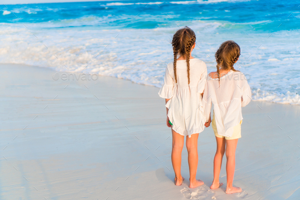 Adorable little sisters together on the beach - Stock Photo - Images