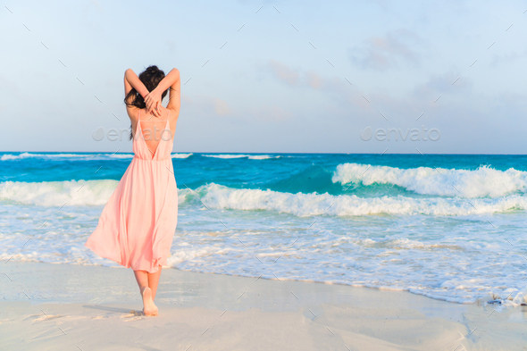 Young beautiful woman in dress on the seashore on sunset - Stock Photo - Images