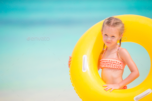 Adorable girl with inflatable rubber circle on white beach - Stock Photo - Images