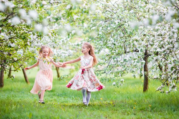 Beautiful girls in blooming apple tree garden enjoy warm spring day - Stock Photo - Images