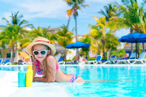 Little girl with bottle of sun cream in swimming pool - Stock Photo - Images