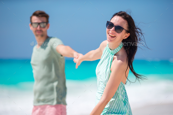 Smiling couple holding hands on the beach - Stock Photo - Images