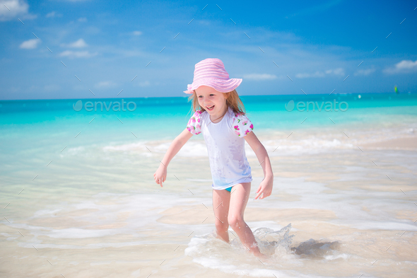 Adorable little girl at beach having a lot of fun in shallow water - Stock Photo - Images